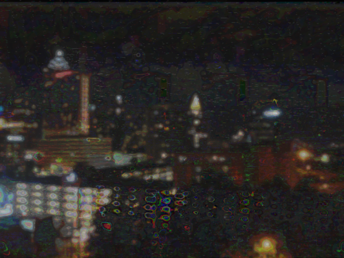 a cityscape at night, blurred with lights on every building, and some blobs that were trees nearer the viewer. there are lines of static and discolored blobs throughout the image, as well as outlines around some shapes.